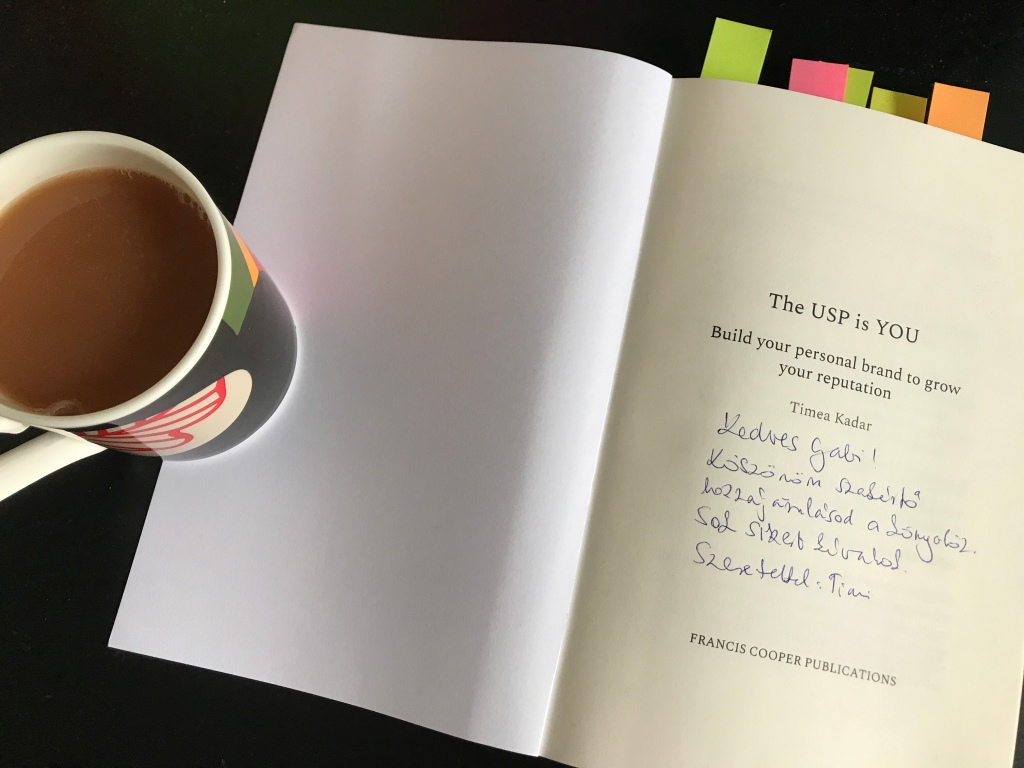 English breakfast tea with a touch of milk, The USP is You book with cover open, and Timea's kind words addressing Gabriella Ferenczi, in Hungarian